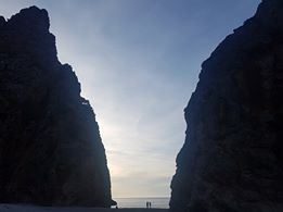 A photo of cliffs at a beach silhouetted against the sunset