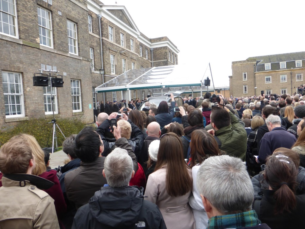 Crowds wait to view the coffin being carried into the hearse on Sunday